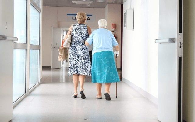 Fire doors help open with people walking through hospital corridor